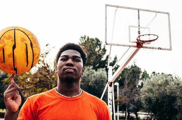 彼の手でバスケットボールを回転する黒いアフロの少年の肖像画。背景のバスケットボールのバスケット。