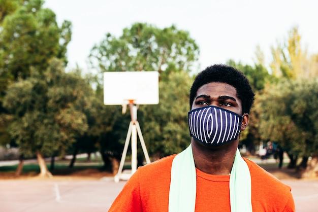 얼굴 마스크와 길거리 농구 코트에서 녹색 수건으로 흑인 아프리카 소년의 초상화. 전염병 시대의 스포츠.