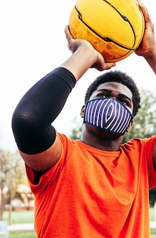 바구니에 공을 던지는 얼굴 마스크와 흑인 아프리카 소년의 초상화. 전염병 시대의 스포츠.