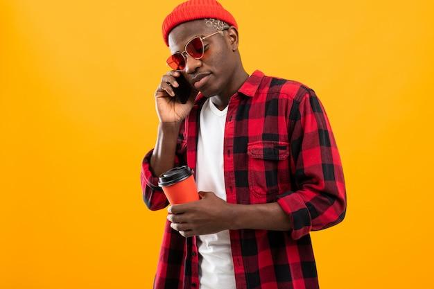 電話黄色の背景のコーヒーブレークにドリンクカップを保持している市松模様の赤シャツを着ている黒いアメリカ人ハンサムなスタイリッシュな男の肖像