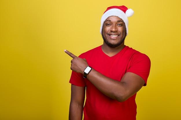 Портрет темнокожего парня в шляпе санта-клауса, указывающего вверх указательным пальцем