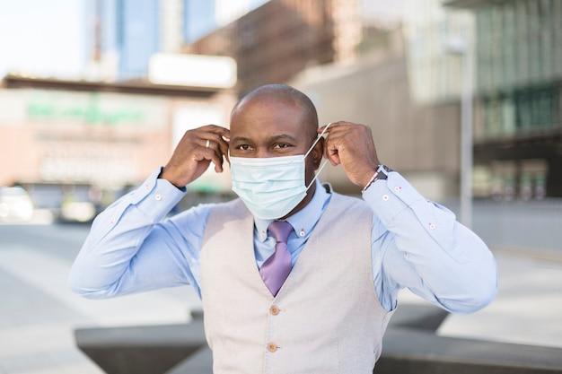 医療用マスクを顔につけている黒人男性の肖像画。