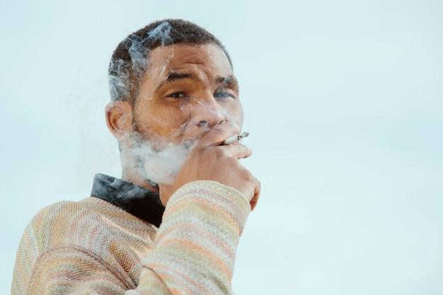 흑인 남자, 흡연, 카메라를 찾고 초상화.