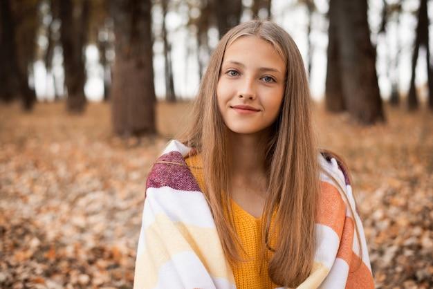 공원에서 따뜻한 격자 무늬의 금발 소녀의 초상화