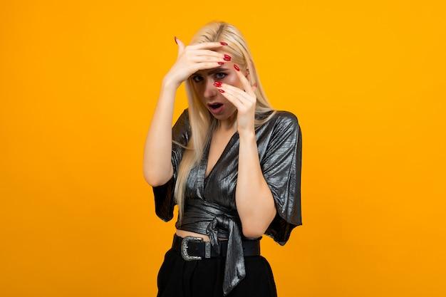 노란색 스튜디오 배경에 불안 감정을 보여주는 금발의 젊은 여자의 초상화
