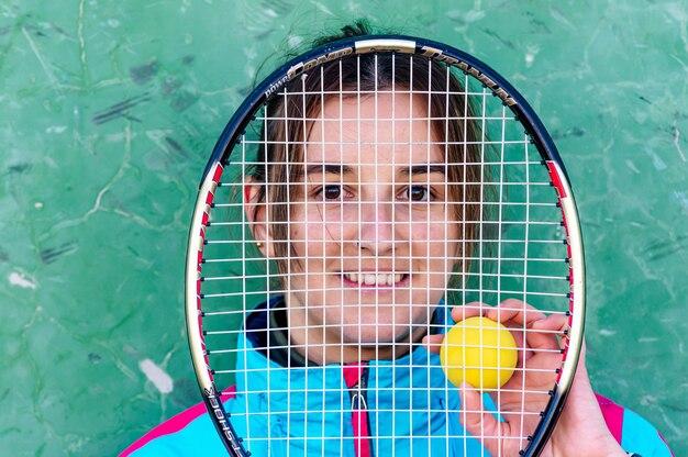 Портрет белокурой женщины кавказа с теннисной ракеткой в ее лице.