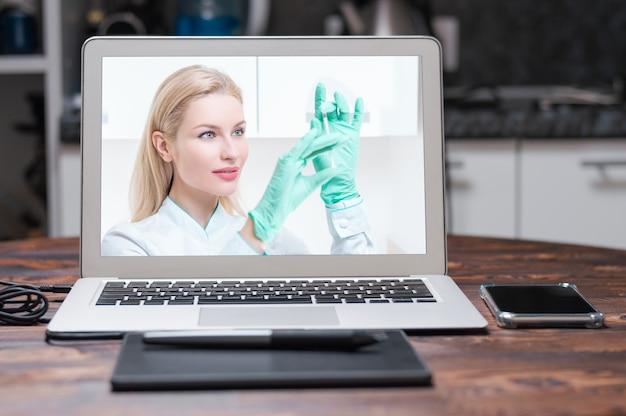 彼女の手に注射器を持つ医療用ガウンのブロンドの女の子の肖像画。医療センターの広告。ミクストメディア