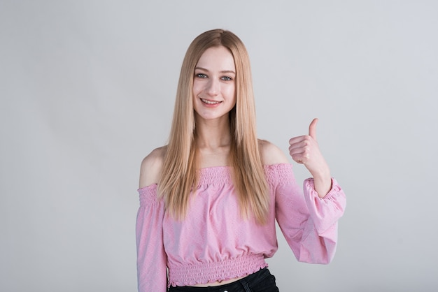 Портрет блондинки, которая показывает палец вверх в студии на белом фоне