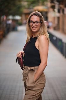 바르셀로나 시내에서 사진 촬영을 위해 포즈를 취한 안경을 쓴 금발 소녀의 초상화.