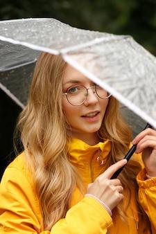 클로즈업 우산을 쓴 노란 비옷을 입은 금발의 초상화