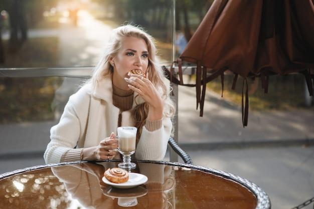 케이크, 긴 머리, 베이지 색 코트를 먹고 카페에서 테이블에 금발 아가씨의 초상화.
