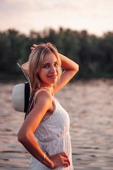 Портрет блондинки на фоне реки красивая молодая счастливая женщина позирует на закате в ...