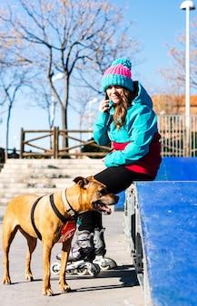 Портрет блондинки женщины на роликах со своей собакой. сидят на рампе. звонит по мобильному телефону. концепция городского катания.