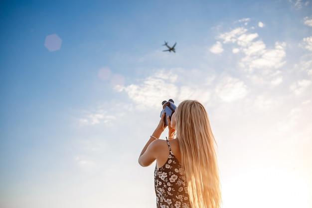 Портрет блондинки в платье с цветочным принтом с винтажной видеокамерой в виноградном поле записывает видео взлетающего самолета
