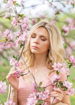 Портрет блондинка в розовых цветах. весенний сад