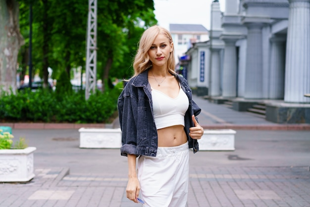 街でポーズをとって白いトラックスーツで白人民族の若い美しい女性の街の通りに金髪の女性の肖像画