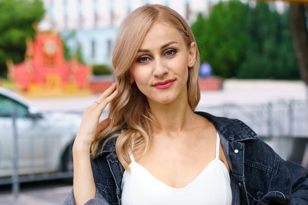 街でポーズをとる白いトラックスーツを着た白人民族の若い美しい女性の街の通りに金髪の女性の肖像画