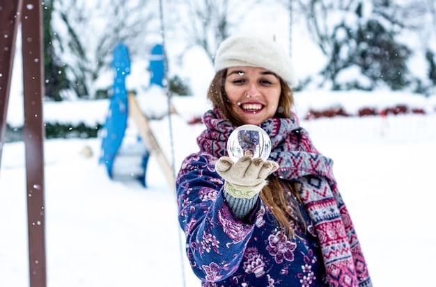 눈 덮인 공원에서 수정 구슬을 들고 베레모, 재킷 및 스카프를 입고 금발 여자의 초상화.