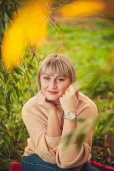 숲속의 공터에서 빨간 담요에 앉아 짧은 머리를 한 금발의 여성의 초상화. 가을 숲에서 야외 산책과 휴식
