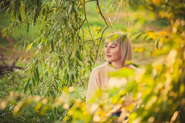 숲속의 공터에서 빨간 담요에 앉아 짧은 머리를 한 금발 여성의 초상화