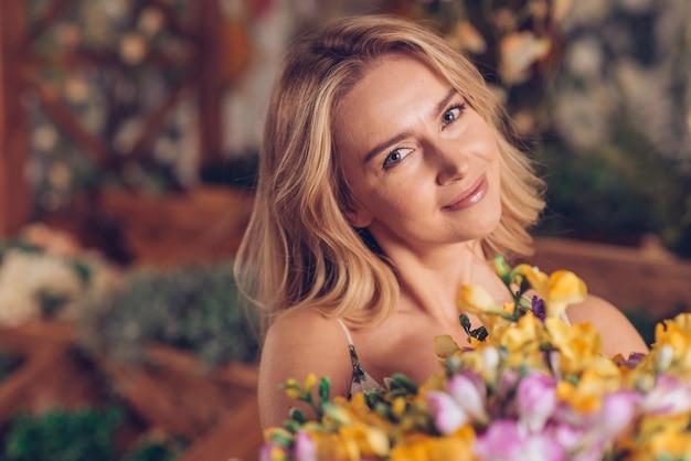 花の花束を持つ金髪の若い女性の肖像画