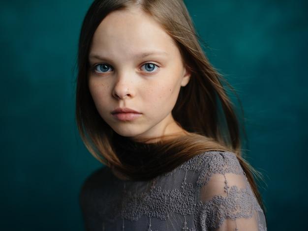 灰色のドレスを着た青い目の少女の肖像画