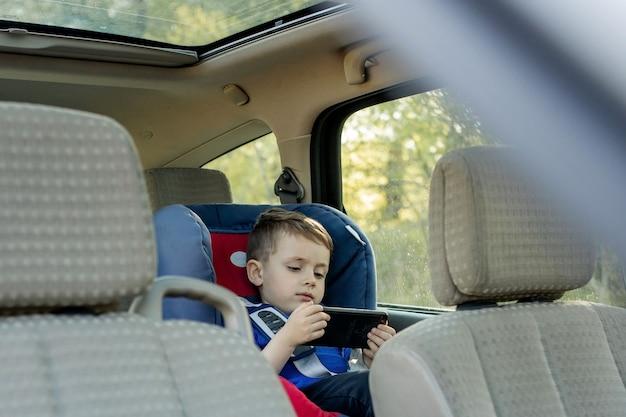Портрет скучающего маленького мальчика, сидящего в автокресле. безопасность перевозки детей.