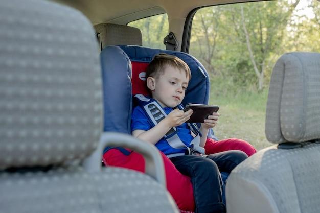 車の座席に座っている退屈少年の肖像画。子供の輸送の安全性。