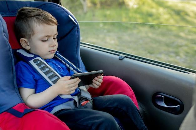 Портрет скучающего маленького мальчика, сидящего в автокресле