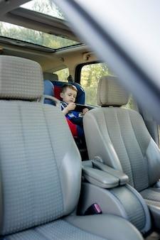 車の座席に座っている退屈少年のポートレート