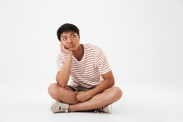 Портрет скучающего молодого азиатского человека, сидящего с ногами