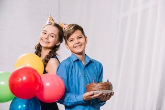 Портрет мальчика и девочки, держащей разноцветные воздушные шары и торт на тарелку