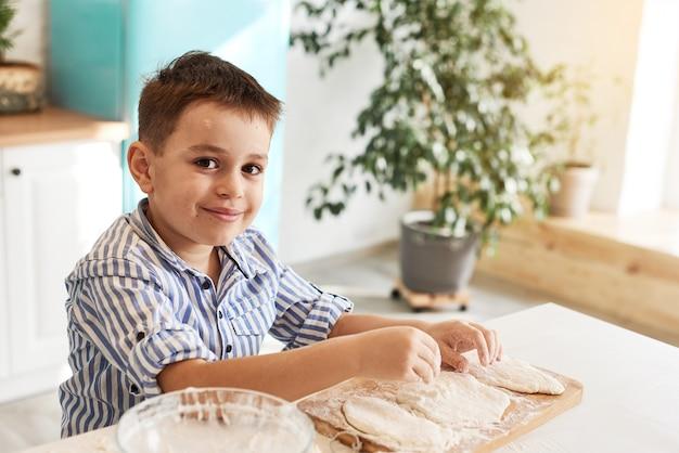 台所のテーブルで男の子の肖像画。彼が生地を転がす前に。彼の顔は小麦粉で少し汚れています。