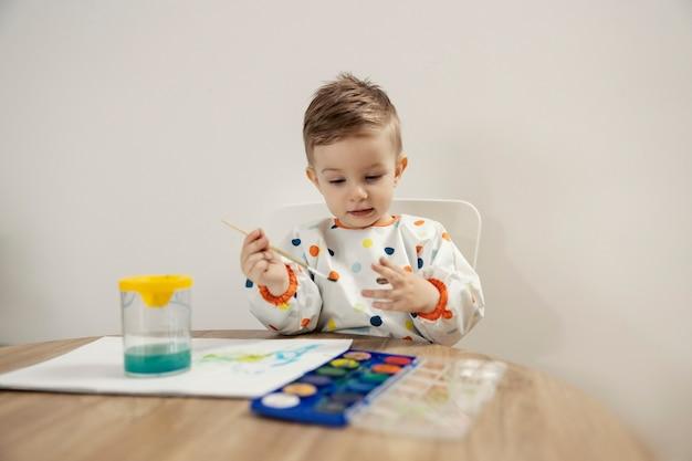 Портрет мальчика, рисующего акварелью. симпатичный малыш-мальчик, одетый в разноцветный горошек, сидит за столом в помещении и рисует кистью на бумаге. детство и развитие творческих способностей