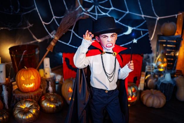 グランジの背景に吸血鬼と帽子の衣装を着た少年の肖像画。ハロウィーンパーティー。