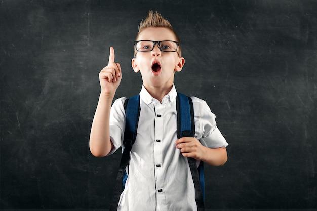 Портрет мальчика из начальной школы на фоне школьной доски
