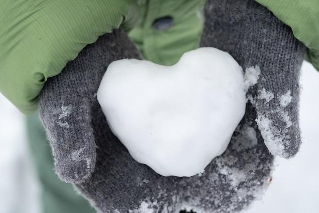 Портрет мальчика, держащего сердце зимой