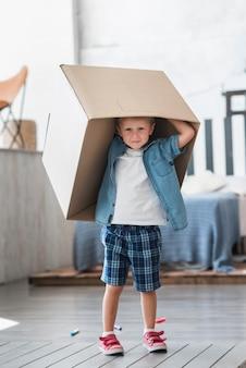 寝室の彼の頭の上に段ボール箱を持っている少年の肖像