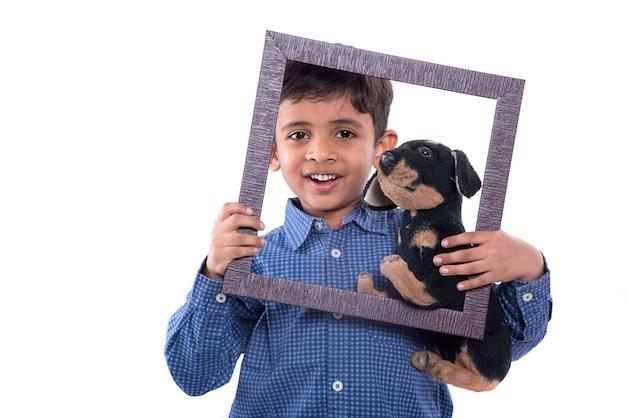 Портрет мальчика, держащего мягкую игрушку в рамке на белом фоне