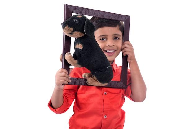 白い壁にフレームとぬいぐるみペットを保持している少年の肖像画