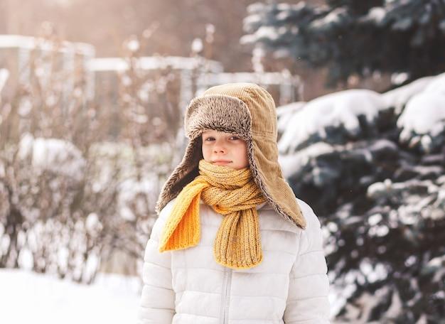 晴れた日の冬の冬の帽子をかぶった少年の肖像画