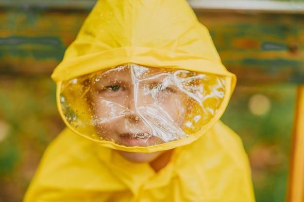 雨の間に路上で黄色いレインコートを着た少年の肖像画。レインフードプロテクション。顔を覆う透明なフードの雨滴。散歩のための子供のための明るい服。