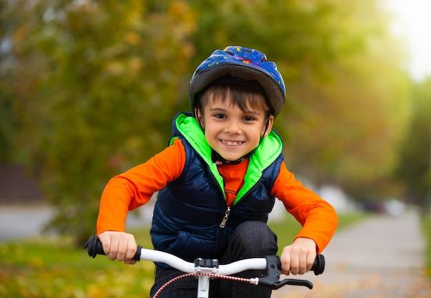 公園の少年の肖像画。小さな子供がヘルメットをかぶって、秋の日にサイクリング。アクティブで健康的なアウトドアスポーツ。