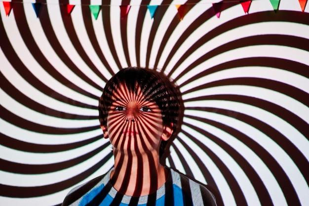 らせん状に投影された背景の少年の肖像画。