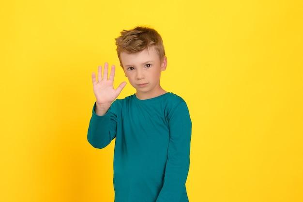 カメラの停止ジェスチャーに彼の手のひらを示す黄色の背景の少年の肖像画