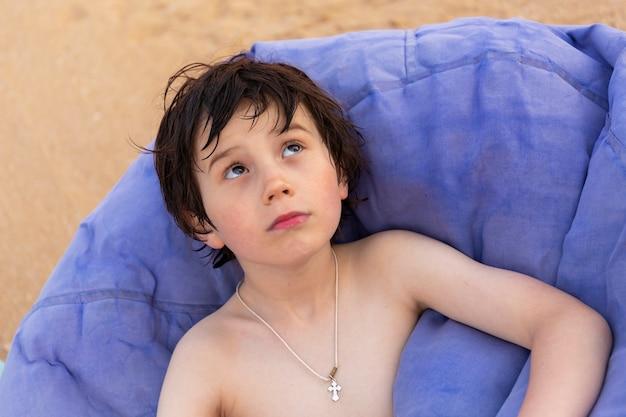 Портрет мальчика, сидящего на кресле-мешке на пляже курорта летом.