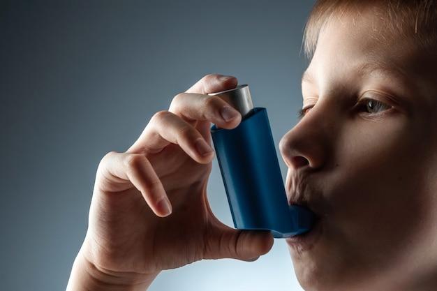 염증성 질환, 호흡 곤란을 치료하기 위해 천식 흡입기를 사용하는 소년의 초상화. 기침, 알레르기, 호흡기 질환 치료의 개념.