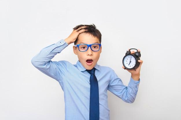 무서워하는 얼굴을 가진 소년의 초상화와 그의 손에 검은 알람 시계