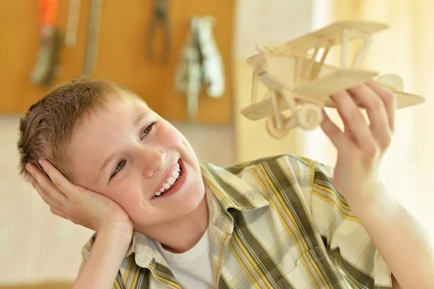 木製の飛行機を持つ少年の肖像画