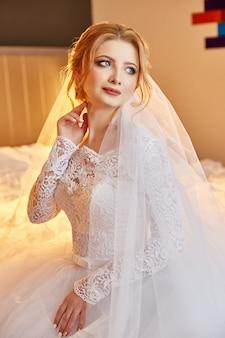 ベッドの上のシックな白いウェディングドレスに座って、結婚式の準備をしている花嫁の肖像画。白いドレスと彼女の頭の上のベールのブロンドの女性。花嫁は花婿を待っています